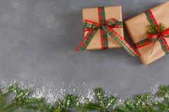 Χειροποίητα κιβώτια δώρων Χριστουγέννων, τοπ άποψη, διάστημα αντιγράφων στο γκρίζο επιτραπέζιο υπόβαθρο Το FIR, διακοσμημένο χιόν Στοκ Εικόνες