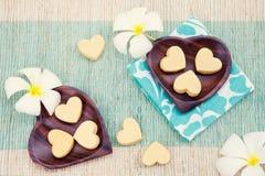 Χειροποίητα μπισκότα μορφής καρδιών στο ξύλινο πιάτο και την μπλε άποψη υποβάθρου πετσετών υπαίθρια τοπ Στοκ Εικόνα