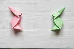 Χειροποίητα ρόδινα, πράσινα λαγουδάκια origami εγγράφου στο άσπρο σανίδων υπόβαθρο πινάκων σιταποθηκών ξύλινο Στοκ φωτογραφία με δικαίωμα ελεύθερης χρήσης
