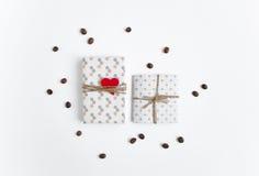 Χειροποίητα δώρα στο άσπρο υπόβαθρο που διακοσμείται με τα φασόλια καρδιών και καφέ Η τοπ άποψη, επίπεδη βάζει Στοκ Εικόνες