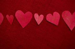 Χειροποίητες κόκκινες καρδιές στην κόκκινη ανασκόπηση Στοκ εικόνες με δικαίωμα ελεύθερης χρήσης