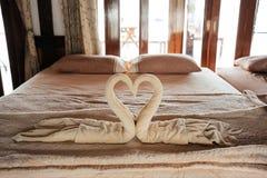 Χειροποίητες πετσέτες κύκνων ζευγών που τοποθετούνται στο κρεβάτι στο δωμάτιο ξενοδοχείου με το pil Στοκ Εικόνες
