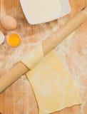 Χειροποίητη ακατέργαστη ζύμη με το αλεύρι και αυγά στον ξύλινο πίνακα με μια κυλώντας καρφίτσα Στοκ φωτογραφίες με δικαίωμα ελεύθερης χρήσης