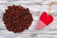 Χειροποίητη καρδιά κοντά στο σωρό καφέ Στοκ φωτογραφία με δικαίωμα ελεύθερης χρήσης