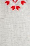 Χειροποίητη κεντητική στοιχείων στο λινάρι από τα κόκκινα και άσπρα νήματα βαμβακιού Ανασκόπηση με την κεντητική Στοκ φωτογραφία με δικαίωμα ελεύθερης χρήσης