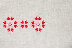 Χειροποίητη κεντητική στοιχείων στο λινό από τα κόκκινα και άσπρα νήματα βαμβακιού Ανασκόπηση με την κεντητική Στοκ Εικόνες