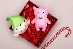 Χειροποίητος ρόδινος χοίρος σε ένα κιβώτιο δώρων με κόκκινο tinsel στοκ εικόνα