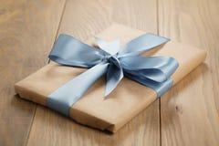 Χειροποίητο κιβώτιο καφετιού εγγράφου δώρων με το μπλε τόξο κορδελλών στον ξύλινο πίνακα Στοκ φωτογραφία με δικαίωμα ελεύθερης χρήσης