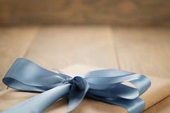 Χειροποίητο κιβώτιο καφετιού εγγράφου δώρων με το μπλε τόξο κορδελλών στον ξύλινο πίνακα Στοκ Εικόνες