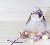 Χειροποίητο κορίτσι κουνελιών που κρατά ένα καλάθι με τα αυγά Πάσχας Άσπρο wo στοκ εικόνες