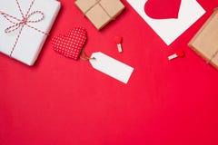 Χειροποίητο μικρό κιβώτιο δώρων με το σύμβολο καρδιών στο κόκκινο υπόβαθρο Στοκ Εικόνα