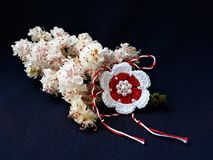 Χειροποίητο πλεγμένο λουλούδι με την κόκκινη και άσπρη σειρά, γνωστή ως Martisor στοκ φωτογραφία