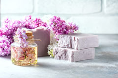 Χειροποίητο σαπούνι, βάζο γυαλιού με το ευώδες πετρέλαιο και ιώδη λουλούδια για τη SPA και aromatherapy Στοκ Φωτογραφία