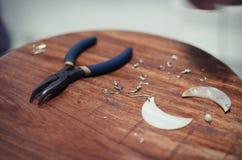 Χειροποίητο σκουλαρίκι που δημιουργεί τη διαδικασία: διάφορα κομμάτια και πένσες επάνω Στοκ Εικόνες