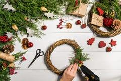 Χειροποίητο diy υπόβαθρο Χριστουγέννων Παραγωγή του στεφανιού και των διακοσμήσεων Χριστουγέννων τεχνών Τοπ άποψη του άσπρου ξύλι Στοκ Εικόνα
