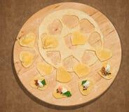 Χειροποίητο ravioli με μορφή της καρδιάς, ανοικτός και κλειστός, που τοποθετείται σε ένα στρογγυλό κεντρικό τεμάχιο του ξύλου Στοκ εικόνα με δικαίωμα ελεύθερης χρήσης