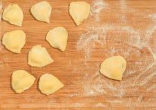Χειροποίητο ravioli με μορφή της καρδιάς που καλύπτεται με το αλεύρι και που τοποθετείται στον ξύλινο πίνακα Στοκ Εικόνες