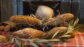 Χειροτεχνικά ψωμιά σε ένα στήθος θησαυρών με το ξύλινο υπόβαθρο στοκ φωτογραφίες