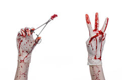 Χειρουργική επέμβαση και θέμα ιατρικής: ο γιατρός αιματηρός παραδίδει το γάντι κρατώντας έναν αιματηρό χειρουργικό σφιγκτήρα με τ Στοκ Φωτογραφίες