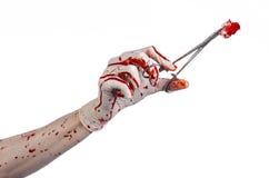 Χειρουργική επέμβαση και θέμα ιατρικής: ο γιατρός αιματηρός παραδίδει το γάντι κρατώντας έναν αιματηρό χειρουργικό σφιγκτήρα με τ Στοκ εικόνες με δικαίωμα ελεύθερης χρήσης