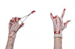Χειρουργική επέμβαση και θέμα ιατρικής: ο γιατρός αιματηρός παραδίδει το γάντι κρατώντας έναν αιματηρό χειρουργικό σφιγκτήρα με τ Στοκ φωτογραφίες με δικαίωμα ελεύθερης χρήσης