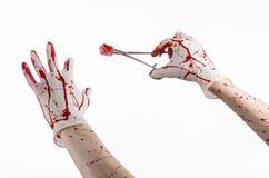 Χειρουργική επέμβαση και θέμα ιατρικής: ο γιατρός αιματηρός παραδίδει το γάντι κρατώντας έναν αιματηρό χειρουργικό σφιγκτήρα με τ Στοκ Εικόνες