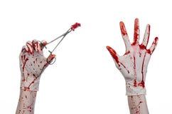 Χειρουργική επέμβαση και θέμα ιατρικής: ο γιατρός αιματηρός παραδίδει το γάντι κρατώντας έναν αιματηρό χειρουργικό σφιγκτήρα με τ Στοκ Εικόνα