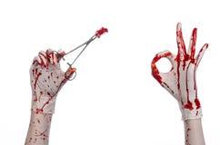 Χειρουργική επέμβαση και θέμα ιατρικής: ο γιατρός αιματηρός παραδίδει το γάντι κρατώντας έναν αιματηρό χειρουργικό σφιγκτήρα με τ Στοκ εικόνα με δικαίωμα ελεύθερης χρήσης