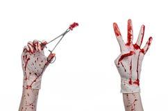 Χειρουργική επέμβαση και θέμα ιατρικής: ο γιατρός αιματηρός παραδίδει το γάντι κρατώντας έναν αιματηρό χειρουργικό σφιγκτήρα με τ Στοκ φωτογραφία με δικαίωμα ελεύθερης χρήσης