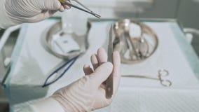 Χειρουργικός πίνακας με τα αποστειρωμένα ιατρικά όργανα Ο βοηθός δίνει στο χειρούργο τη λεπίδα χειρουργικών νυστεριών Κινηματογρά απόθεμα βίντεο
