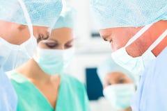 Χειρούργοι που αναπτύσσουν δραστηριότητες στο δωμάτιο θεάτρων λειτουργίας Στοκ φωτογραφία με δικαίωμα ελεύθερης χρήσης