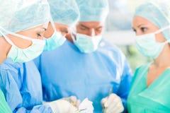 Χειρούργοι που λειτουργούν τον ασθενή στο θέατρο λειτουργίας Στοκ Εικόνες
