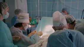 Χειρούργοι που ολοκληρώνουν τη χειρουργική επέμβαση εμφύτευσης μοσχευμάτων απόθεμα βίντεο