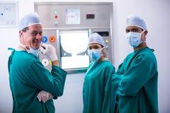 Χειρούργοι που συζητούν μια έκθεση σχετικά με το χειρουργικό όργανο ελέγχου στο δωμάτιο λειτουργίας στοκ εικόνες