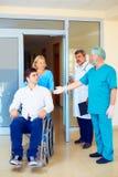 Χειρούργος και ιατρικό προσωπικό που μιλούν με το νέο ενήλικο άτομο στην αναπηρική καρέκλα, στο νοσοκομείο Στοκ φωτογραφία με δικαίωμα ελεύθερης χρήσης