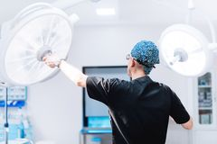 χειρούργος που παίρνει έτοιμος για τη χειρουργική επέμβαση, τους λαμπτήρες καθορισμού και το φως ρύθμισης στο δωμάτιο λειτουργίας Στοκ Εικόνες