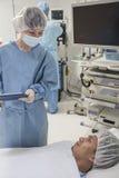 Χειρούργος που συμβουλεύεται έναν ασθενή, που παίρνει έτοιμο για τη χειρουργική επέμβαση Στοκ Φωτογραφία