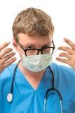 Χειρούργος που φορά τα γυαλιά που τίθενται στην προστατευτική μάσκα Στοκ Εικόνες