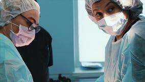 Χειρούργος στην εργασία μια ομάδα των επαγγελματικών χειρούργων εκτελεί τη χειρουργική επέμβαση στον ασθενή Πραγματικό λειτουργού απόθεμα βίντεο