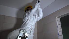 Χειρωνακτική τρυπώντας με τρυπάνι τρύπα εργαζομένων στην ανώτατη γυψοσανίδα για το οδηγημένο μοντάρισμα φωτισμού απόθεμα βίντεο