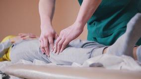 Χειρωνακτικός θεράπων που τρίβει μια νέα γυναίκα που βρίσκεται σε έναν πίνακα μασάζ, που τεντώνει τα γόνατά της φιλμ μικρού μήκους
