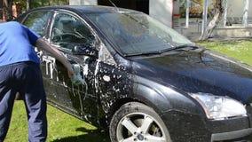 Χειρωνακτικός καθαρισμός πλύσης αυτοκινήτων χεριών με τον αφρό και το σφουγγάρι στο ναυπηγείο απόθεμα βίντεο