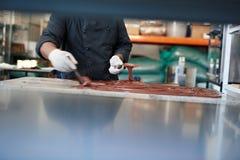 Χειρωνακτικός κατασκευαστής βιομηχανιών ζαχαρωδών προϊόντων που διαδίδει τη λειωμένη σοκολάτα σε έναν πίνακα στοκ εικόνες