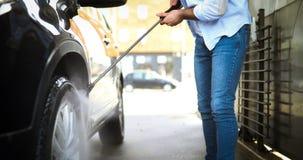 Χειρωνακτικό πλύσιμο αυτοκινήτων με το διατηρημένο σταθερή ατμοσφαιρική πίεση νερό στο πλύσιμο αυτοκινήτων Στοκ Φωτογραφίες