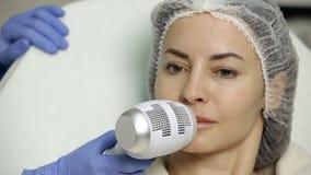 Χειλική αύξηση στο σαλόνι ομορφιάς το cosmetologist εφαρμόζει το κρύο μετά από τη διαδικασία για το αναισθητικό απόθεμα βίντεο