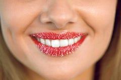 Χειλική προσοχή Το χαμόγελο γυναικών με τα άσπρα δόντια, ζάχαρη τρίβει στα χείλια στοκ εικόνες