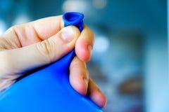 Χεριών δεσμών στενός επάνω υποβάθρου μπαλονιών μπλε - ρίξτε την υπηρεσία προετοιμασιών κομμάτων στοκ φωτογραφίες