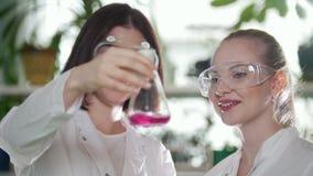 χημικό εργαστήριο Δύο νέες γυναίκες που εξετάζουν τη φιάλη με το ρόδινο υγρό σε το και αξιολογούν το αποτέλεσμα Χαμόγελο φιλμ μικρού μήκους