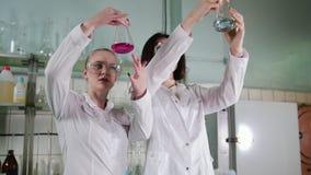 χημικό εργαστήριο Δύο νέοι τεχνικοί εργαστηρίων παίρνουν τις φιάλες από τον πίνακα στα χέρια τους και την εξέταση τον απόθεμα βίντεο