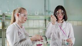 χημικό εργαστήριο Δύο νέοι τεχνικοί εργαστηρίων που κάνουν τα πειράματα με τα υγρά φιλμ μικρού μήκους